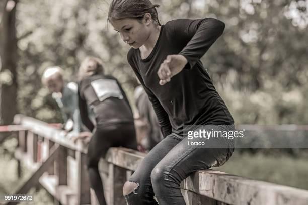 個別代女性子供の障害物コースを実行公共泥でスポーティな楽しい時を過す - 男らしさ ストックフォトと画像