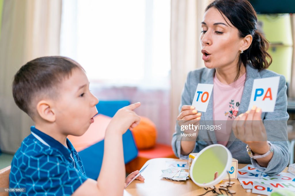 Individual Primary Education. Teacher and Pupil at Reading Lesson : Stock Photo