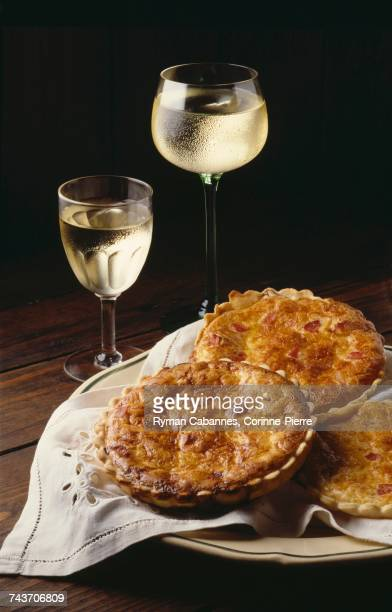 Individual quiches and two glasses of white wine