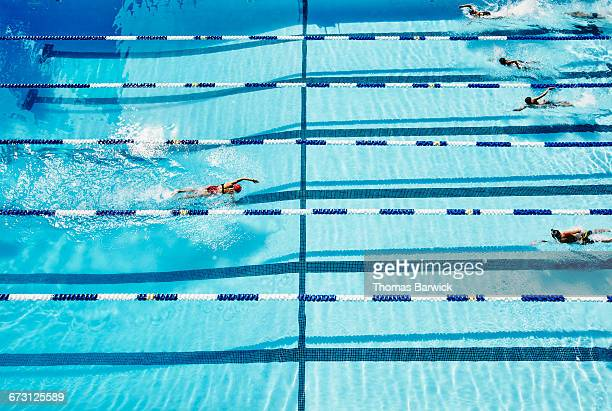 Individual swimmer swimming toward other swimmers