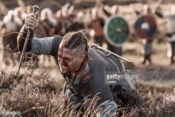 a individual viking warrior in front of a hoard of weapon wielding warriors in the countryside - historical clothing stock pictures, royalty-free photos & images