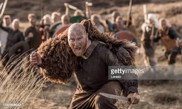 a individual viking warrior in front of a hoard of weapon wielding warriors in the countryside - history stock pictures, royalty-free photos & images