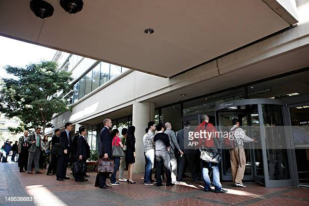 Individuals line up to enter the Robert F Peckham United States Courthouse Building to watch Apple and Samsung face each other in federal district...