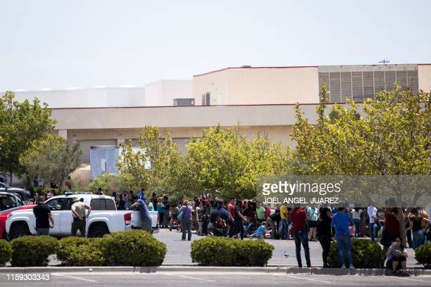 Individuals that were evacuated sit in a parking lot across from a WalMart where a shooting occurred at Cielo Vista Mall in El Paso Texas Saturday...