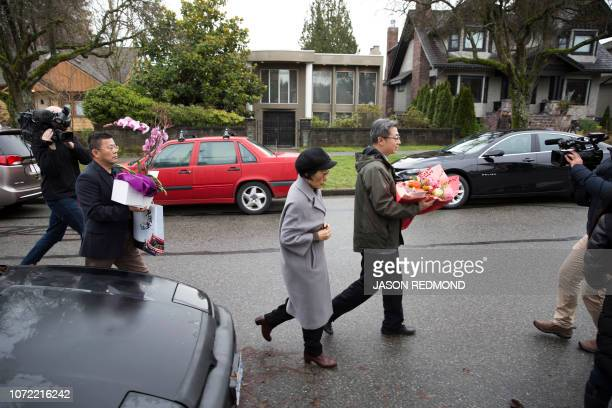 Individuals with flowers exiting a vehicle with consular plates arrive at the residence of Huawei Technologies Chief Financial Officer Meng Wanzhou...