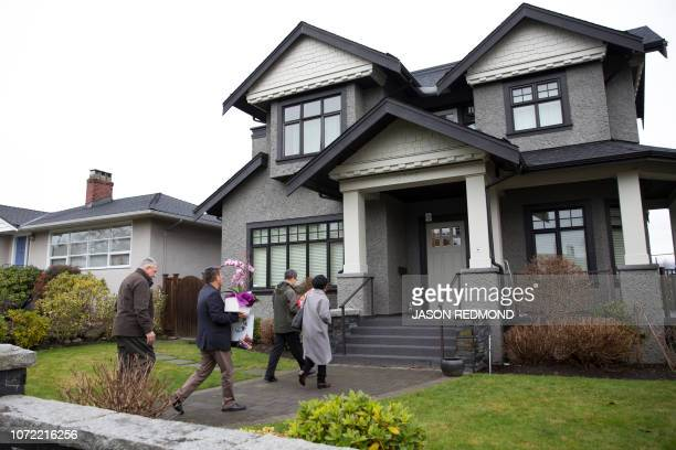 Individuals with flowers exiting from a vehicle with consular plates arrive at the residence of Huawei Technologies Chief Financial Officer Meng...