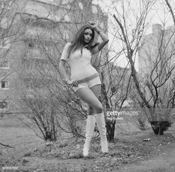 Indo-Guyanese-British actress and fashion model Shakira Caine wearing white playsuit with bullet belt and white boots, UK, 27th November 1972.