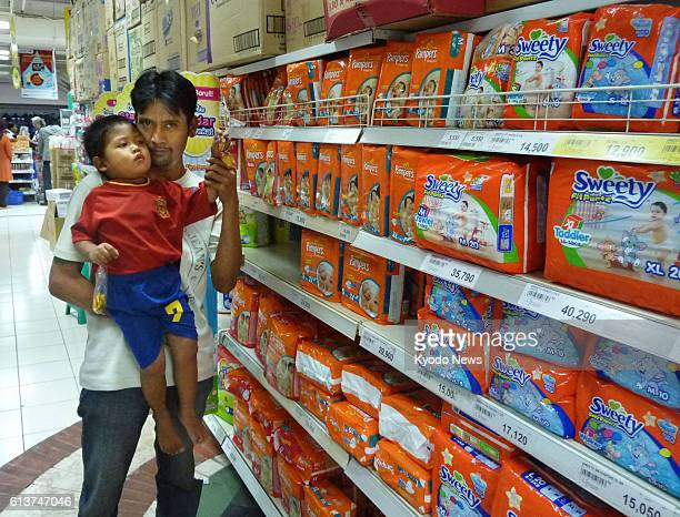 JAKARTA Indonesia A man with a child checks disposable diapers at a supermarket in Jakarta on Aug 14 2012 Disposable diapers have gradually become...