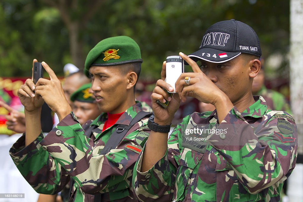 Indonesia army soldiers take pictures on their mobile phones during the 68th anniversary commemoration of the Indonesian Military or TNI on October 5, 2013 in Bintan Island, Indonesia. This year's TNI anniversary was organised under the theme 'Professional, Militate, Solid and Strong TNI-people.'