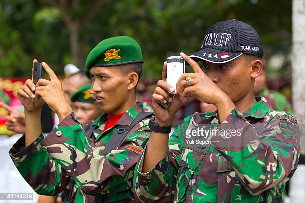Indonesia army soldiers take pictures on their mobile phones during the 68th anniversary commemoration of the Indonesian Military or TNI on October...