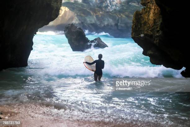 Indonesia, Bali, back view of surfer carrying surfboard