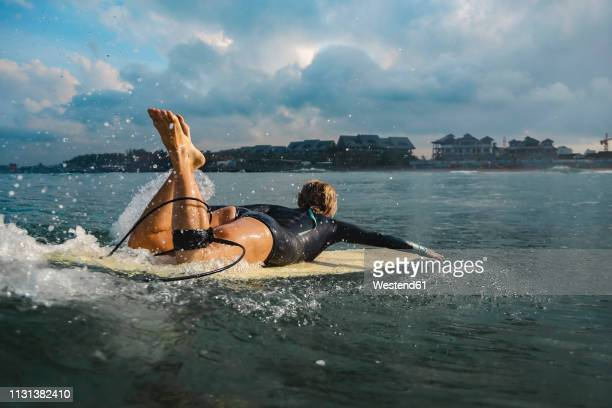 indonesia, bali, canggu, female surfer lying on surfboard - paddling stock pictures, royalty-free photos & images