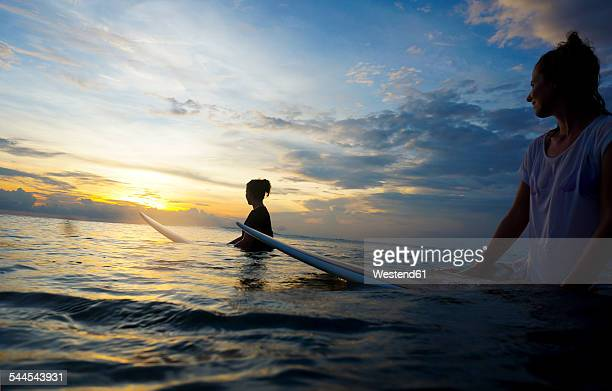 Indonesia, Bali, Canggu, two female surfer in the water watching sun