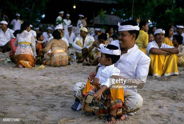 Indonesia Bali Jimbaran Bay Beach Offerings To Gods Of Sea Father Son