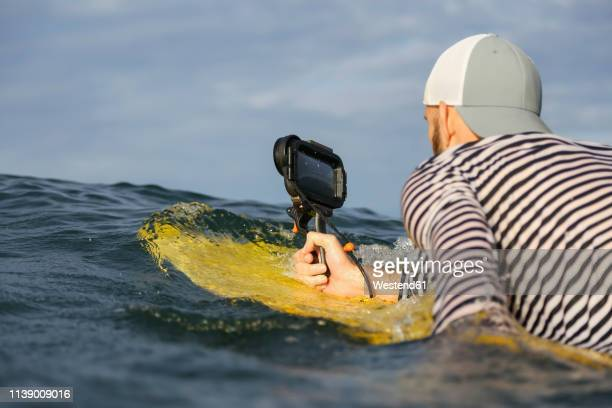 indonesia, bali, man with waterproof smartphone in the sea - photographe professionnel photos et images de collection