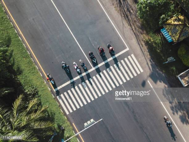 indonesia, bali, sanur, aerial view of motorbikes waiting at zebra crossing on the road - tilt stock pictures, royalty-free photos & images