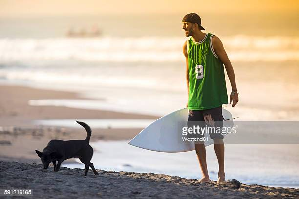 Indonesia, Bali, surfer and dog on the beach