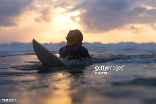 Indonesia, Bali, surfer in the ocean at sunrise