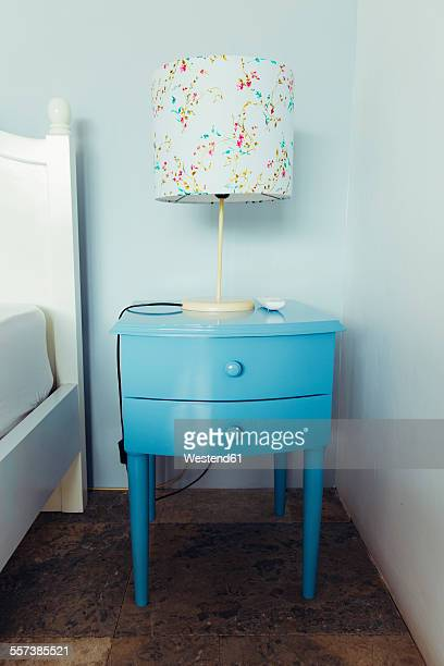 Indonesia, Bali, table lamp and blue bedside cabinet in bedroom of a holiday villa