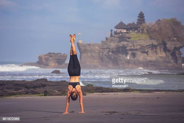 Indonesia, Bali, Tanah Lot, woman doing a handstand on the beach