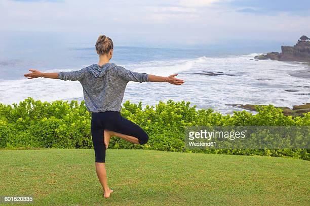 Indonesia, Bali, Tanah Lot, woman practising yoga at the coast