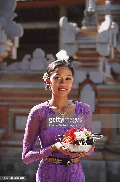 Indonesia, Bali, Ubud, young woman bringing offerings to temple