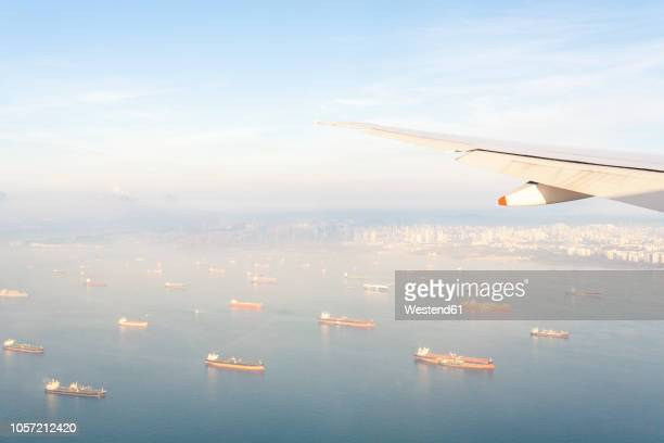 indonesia, bali, wing of an airplane above the sea - indonesia logistics ストックフォトと画像