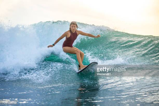 Indonesia, Bali, woman surfing on a wave