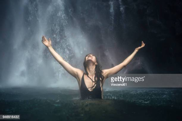 Indonesia, Bali, young woman bathing at Sekumpul waterfall