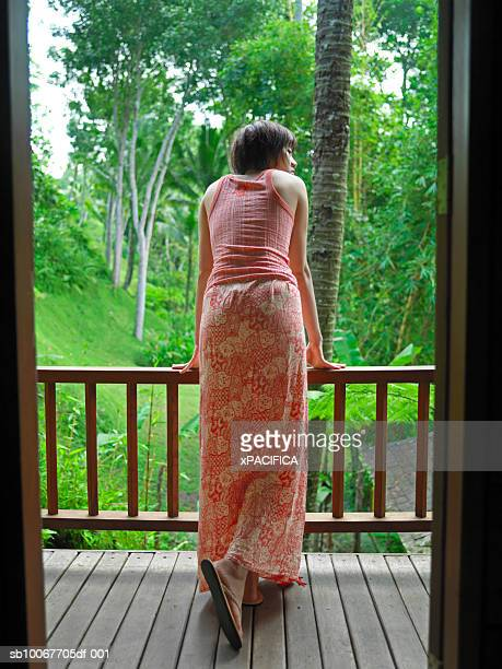 Indonesia, Bali, young woman on balcony in tropical forest, rear view