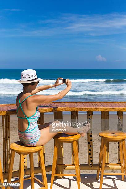 Indonesia, Bali, young woman photographing the beach