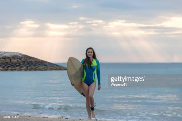 indonesia, bali, young woman with surf board walking at beach - traje de mergulho - fotografias e filmes do acervo