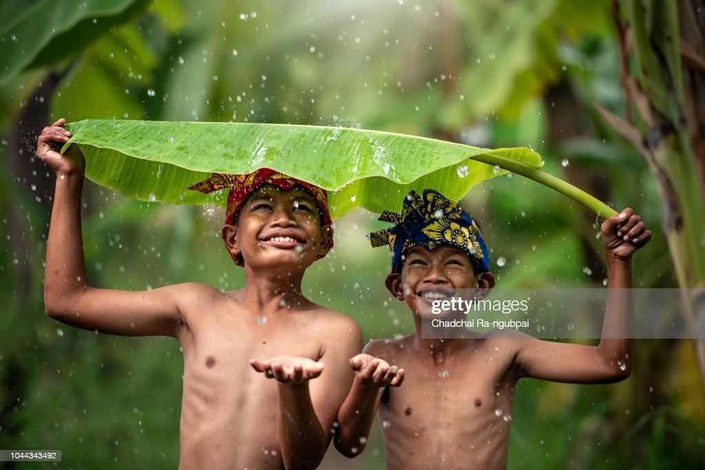 Indonesia children farmer playing rain. Asian kid smile. Indonesian concept. : Bildbanksbilder