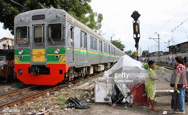 Indonesia - In this file photo from 2010, a used train imported from Japan passes a shack in Jakarta, Indonesia. Most trains operating in the Jakarta...