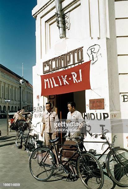 Indonesia Indonésie Jakarta période 19491950 Deux putschistes indonésiens posent devant un bâtiment officiel sous une banderole avec l'inscription en...