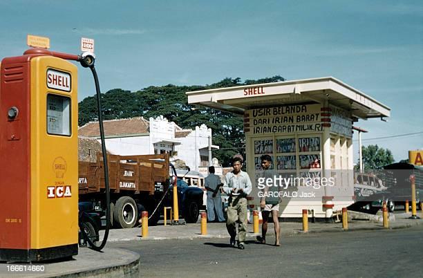 Indonesia Indonésie Jakarta période 19491950 un indonésien se déplace dans une station d'essence des graffitis noirs recouvrant le kiosque du gardien