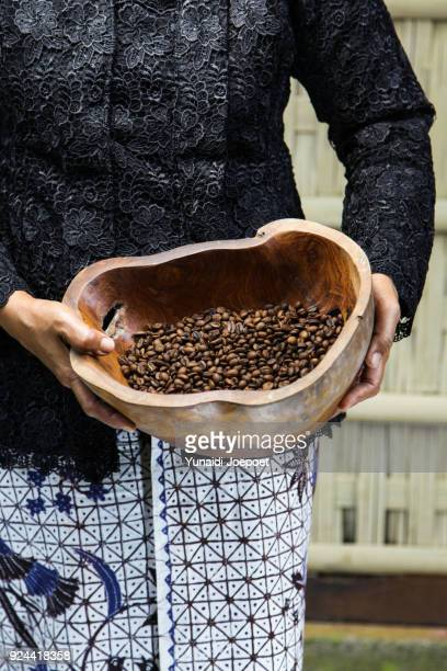 indonesia, local woman holding freshly arabica coffe beans roasted - kintamani district stock pictures, royalty-free photos & images