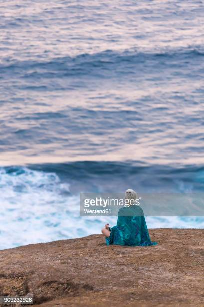 Indonesia, Lombok, woman sitting at the coast looking at view
