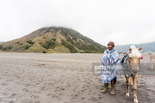 Indonesia man with the horse for tourist rent at Mount Bromo on February 16 2014 in Java IndonesiaMt Bromo is an active volcano and part of the...