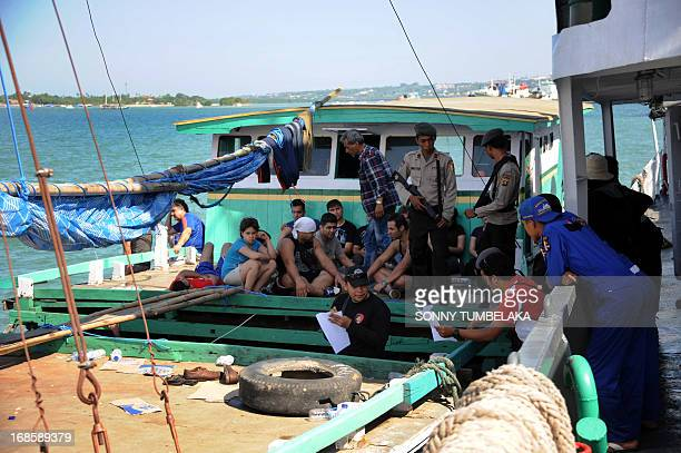 Indonesia marine police stand guard Iranian asylum seekers on a boat at Benoa port in Denpasar on Indonesia's island of Bali on May 12 2013 Indonesia...