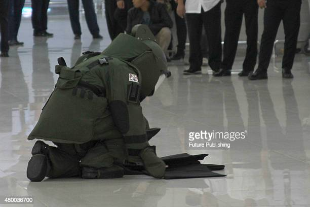 Indonesia Navy Elite bomb squad member tries to defuse a bomb during the antiterror simulation at Juanda Airport in Surabaya on July 08 2015 in East...