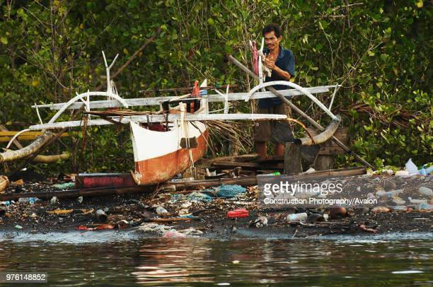 Indonesia, North Sulawesi, near Bitung, Lembeh Strait, Jukung, pollution on the beach.