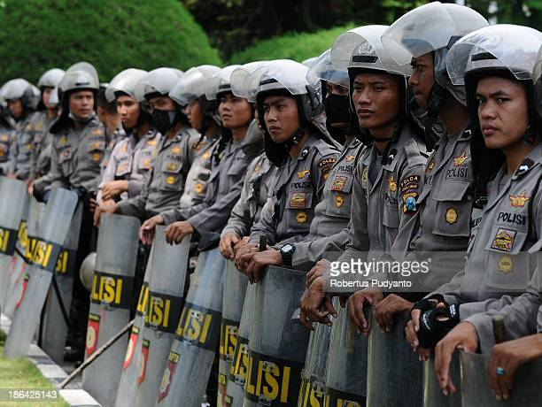 Indonesia Police officers stand guard during a worker and labor unions during a protest demanding higher wages on October 31 2013 in Surabaya...
