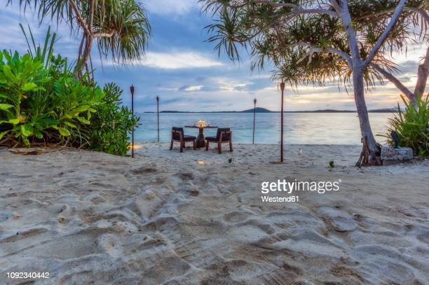 indonesia, riau islands, bintan, table at the beach in the evening - riau images - fotografias e filmes do acervo