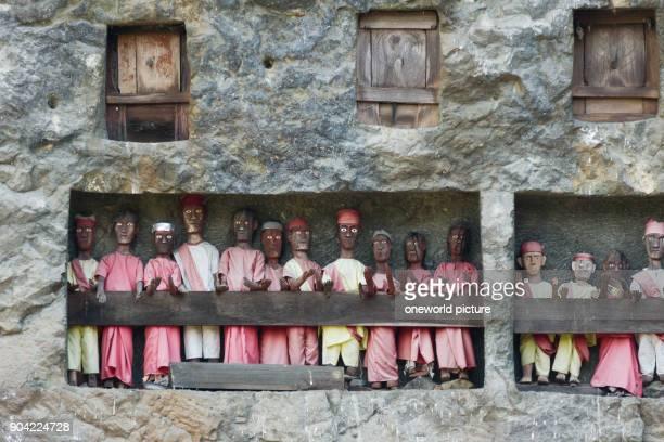 Indonesia Sulawesi Selatan Tana Toraja Torajaland Human wooden figures next to rock tombs dew are carved wooden figures rock tombs death cult