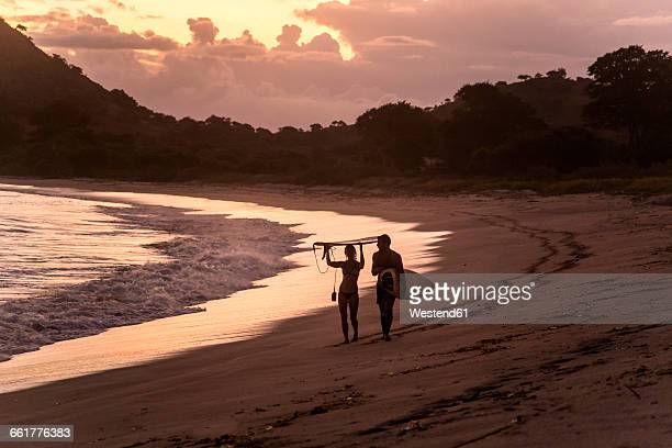 Indonesia, Sumbawa island, Surfer on a beach in the evening