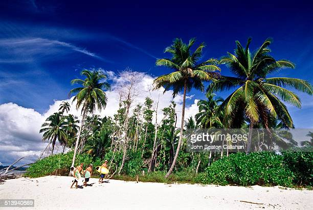 Indonesia West Sumatra Mentawai Islands surfers walking on island beach