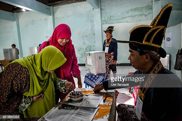 A indonesia woman inks her finger after voting at a polling station as election officers in traditional Kraton soldier known as 'Bergodo' costume...