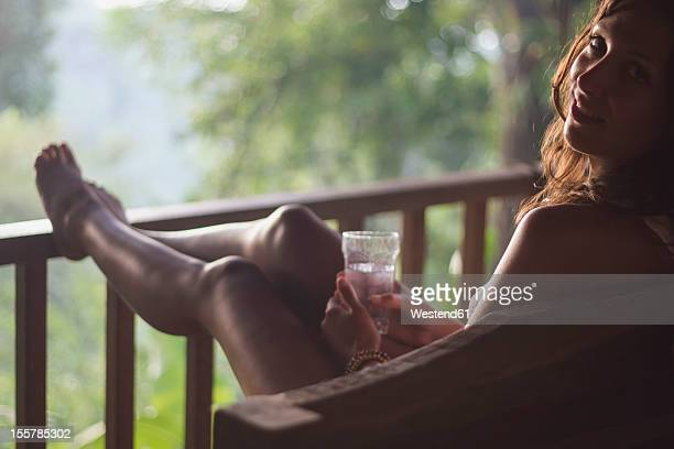 Indonesia, Young woman sitting in sofa with water glass at wooden patio, portrait