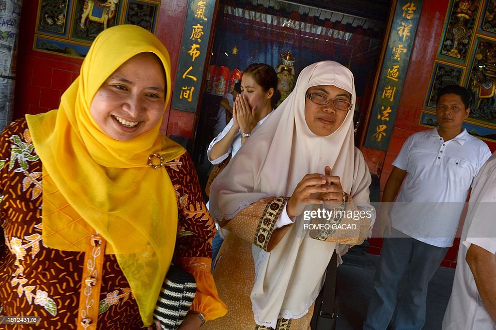 'Indonesia-China-religion-Islam,FEATURE' BY KEVIN PONNIAH In this photograph taken on February 8, 2013, Muslim women Lusi Kusuma (L) and Widi Astuti (R) visit a Buddhist temple in the Indonesian capital city of Jakarta as minority Chinese-Indonesians celebrate the Chinese Lunar New Year. As Indonesia and other countries with Chinese diasporas welcome the Year of the Snake, hardline Islamic leaders have ignited a religious row by declaring the celebrations 'haram' and off limits for Muslims.